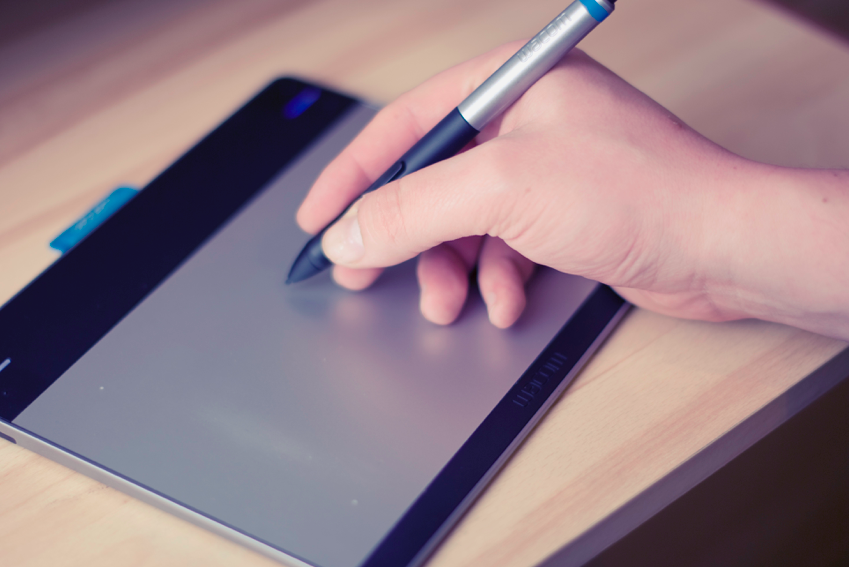 Stock photograph of a hand holding a stylus up to a drawing tablet